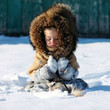 Девочка сидит в снегу