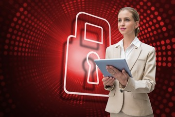 Composite image of lock and businesswoman using tablet