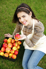 Portrait of happy woman with basket apples against green grass
