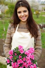Smiling woman holding flower in garden