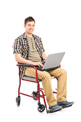 Young man in wheelchair working on a laptop