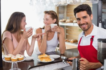 Women drinking coffee with barista at counter in coffee shop