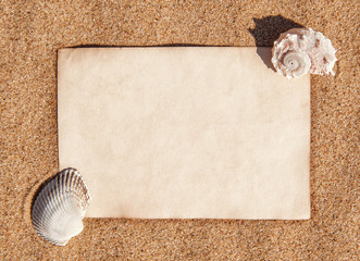 Sheet of paper and seashells on the sand