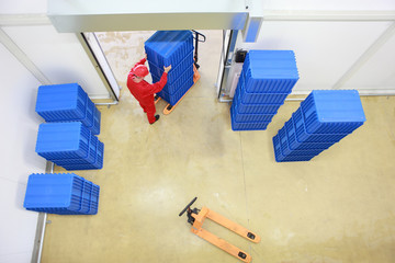 worker loading blue containers to storehouse