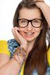 Leinwanddruck Bild - Girl with braces wearing geek glasses isolated