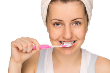 Girl with braces brushing teeth isolated