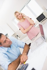 Worried couple with bills and laptop in kitchen