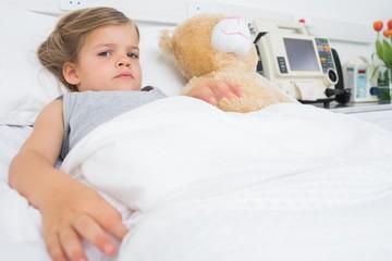 Cute girl lying in hospital bed
