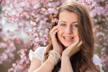 Romantic girl with braces near blossoming tree