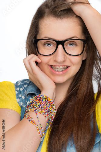 Leinwanddruck Bild Girl with braces wearing geek glasses isolated