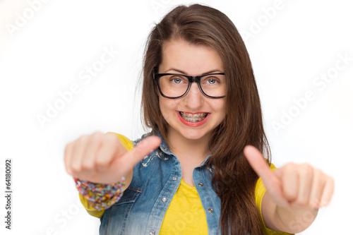 Leinwanddruck Bild Girl in braces showing thumbs up isolated