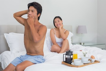Smiling woman watching her boyfriend yawn and stretch