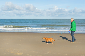 Man walking with dog at the beach