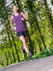 Woman jogging through the forest