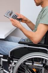 Rollstuhlfahrer mit Taschenrechner