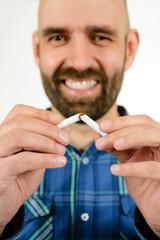 Lachender Mann zerbricht Zigarette