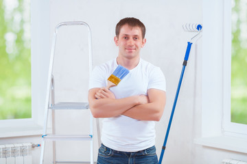 handsome young painter with crossed arms holding blue paintbrush