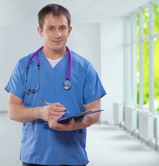 handsome smiling young caucasian doctor wearing blue uniform hol