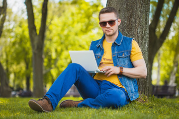 young man in the park sitting on the grass with a laptop