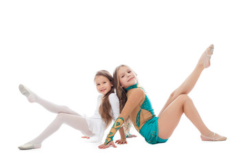 Smiling sisters gymnasts isolated on white