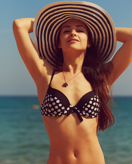 Beautiful bikini woman in hat on sea. Instagram effect