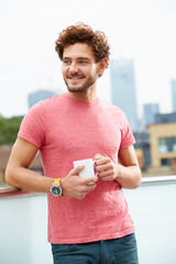 Young Man Relaxing On Roof Terrace With Cup Of Coffee