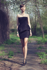 brunette model posing in short black dress