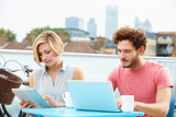 Couple On Roof Terrace Using Laptop And Digital Tablet
