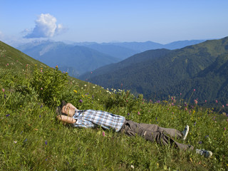 young man lying on grass in mountains in sun