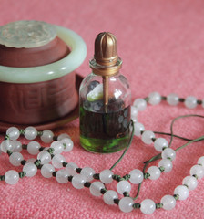 Vial with green butter and the Lotus jewelry made of white stone