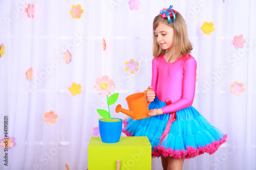 Beautiful small girl in petty skirt watering flowers