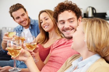 Group Of Friends Enjoying Glass Of Wine At Home