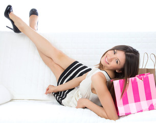 Pretty young woman lying on bed with shopping bags