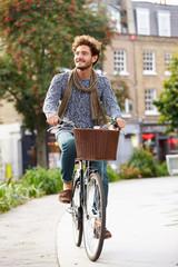 Young Man Cycling Through Urban Park