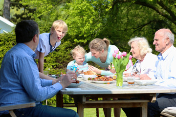 Big family of three generations having lunch outdoors