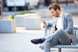 Businessman On Park Bench With Coffee Using Mobile Phone - 64194617