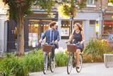 Businesswoman And Businessman Riding Bike Through City Park
