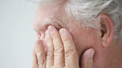 profile view of man rubbing his eyes