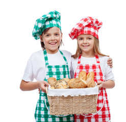 Happy kids with chef hats holding basket with bakery products