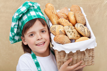 Happy baker boy holding basket with fresh bakery products
