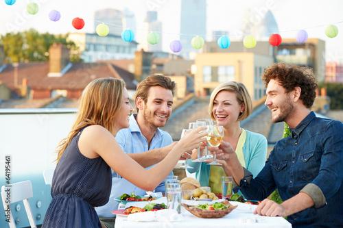 Leinwandbild Motiv Group Of Friends Eating Meal On Rooftop Terrace