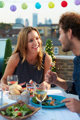 Couple Eating Evening Meal On Rooftop Terrace