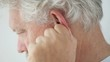 senior man rubs his ear to relieve discomfort