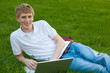 Young boy with laptop computer outside sitting on grass