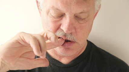 man using finger to clean teeth