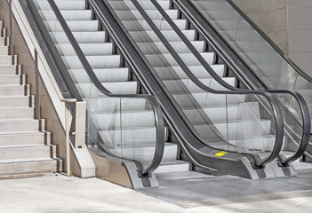 Pair of outdoor modern escalators,stone stairway,tile floor
