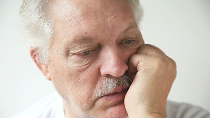 older man leans on his chin and talks