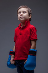 Thoughtful young boy posing in boxing gloves