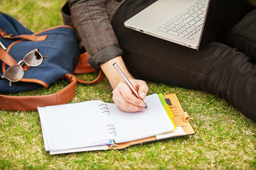 young male student sitting on grass in park and holding a laptop