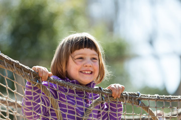 laughing girl climbing on ropes